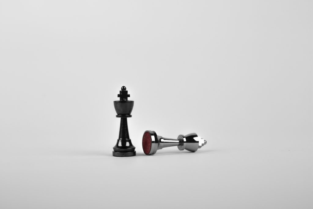1 chess piece down, another upright.